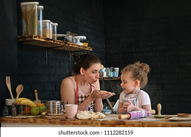 Young mother and daughter prepare cookies in kitchen. They are in aprons. Woman blowing flour in her hands. Girls are fooling around. Family time.