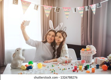 Young mother and daughter prepare for Easter. They sit in room and take selfie on phone camera. Decoration and colorful eggs with painting on table. Easter buny.