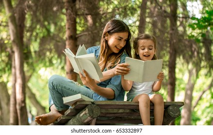 Young mother and daughter reading a book in the woods on a wooden bridge, the concept of a happy family life and family relations