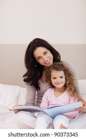 Young mother and daughter reading a book together on the bed