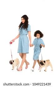young mother and daughter in similar dresses walking with pugs isolated on white