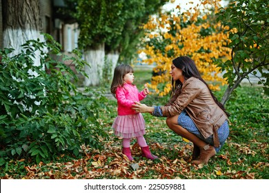 Young mother and daughter walking in the autumn park