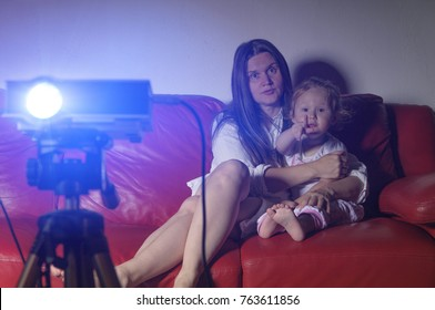 Young mother with daughter watch a cartoon or movie with a projector at home, sitting on couch