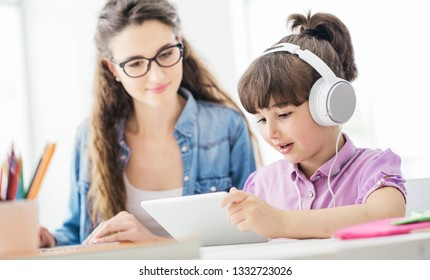 Young mother and daughter watching videos together at home using a digital tablet, the girl is wearing headphones