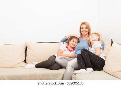 Young mother and daughters  bonding on at home on a couch or sofa