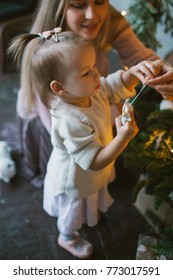Young mother decorating Christmas tree with little daughter in loft apartment