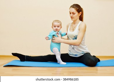 young mother does physical  exercises together with her baby