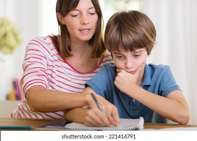Young mother doing homework with her son pointing to something written in his notebook as he stares thoughtfully at the page