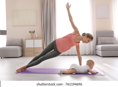 Young mother doing yoga with baby at home
