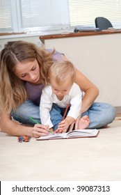 Young mother is drawing with her son
