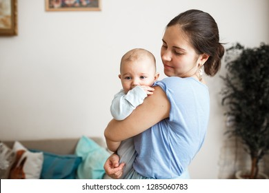 Young mother dressed in light blue t-shirt and skirt is holding her tiny son on her arms in the room at home