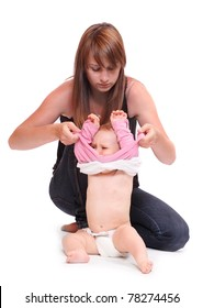 Young mother dressing her baby.