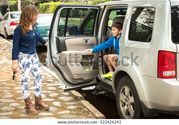 Young mother dropping off her son at soccer practice.