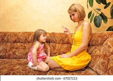 Young mother educating her little daughter at home on sofa