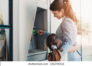 Young mother elegantly dressed with her daughter using ATM machine on city street.