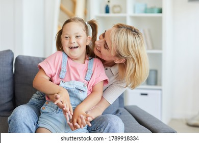 Young mother embracing her disabled child while they sitting on sofa in the room