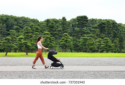 A young mother enjoying the gardens of the imperial palace in Tokyo with her little baby relaxing in his baby carriage.