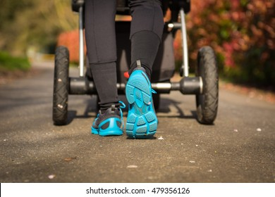 Young mother exercises in a park. Wears blue-gray sport shoes, pushes a pram