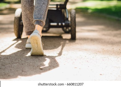 Young mother exercises in a park. Wears gray sport shoes, pushes a pram, close up, back view