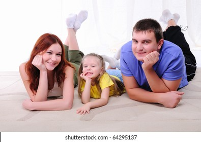 Young mother, a young father and young daughter have fun together