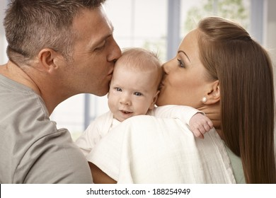 Young mother and father holding newborn baby, kissing head from two sides.