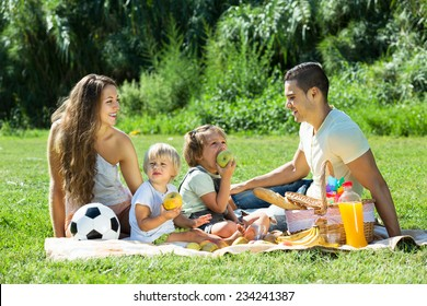Young mother and father with little daughters having holiday with picnic