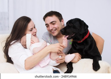 Young mother and father with newborn baby playing with dog