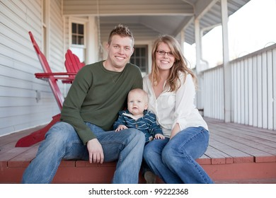 A young mother and father with their young son sitting on their back porch.