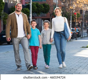 Young mother and father with two kids smiling and taking a walk in the town