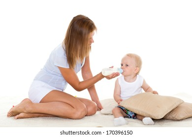 Young mother feeding baby from bottle on a white background. Happy family.