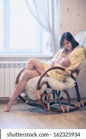 Young mother feeding baby in nursery bedroom