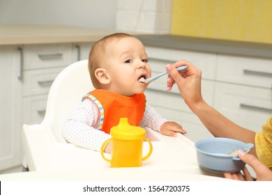 Young mother feeding her little baby at home