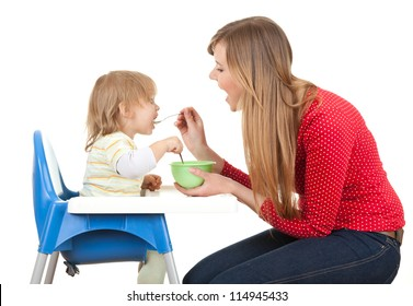 young mother feeding hungry baby in highchair, white background