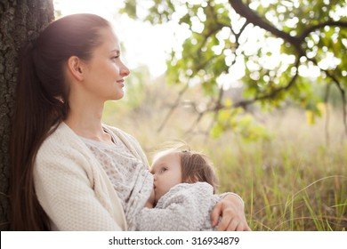young mother feeding toddler outdoors, soft focus