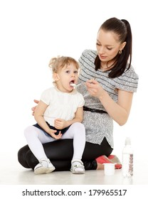 Young mother feeds  her baby on a white background. Happy family.