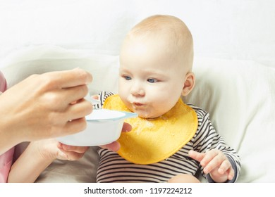 Young mother feeds a small child with a spoon. Concept of starti