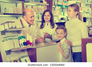 Young mother with a girl consulting two pharmacists at a cash desk at a pharmaceutical store