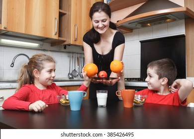 young mother give orange fruits to her daughter and son in the kitchen