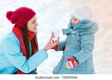 A young mother gives to her little daughter a drink while walking in winter