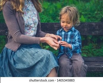 A young mother is giving her toddler a fruit bar on a bench in nature