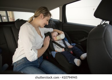 Young mother giving milk in bottle to her little son on car back seat