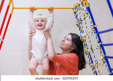 Young mother with happy baby boy doing exercises in sports complex at home. Concept of caring for the baby's health. Happy mom having fun and play with her toddler kid son