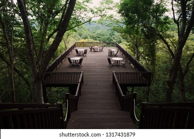 Young mother with happy daughter relaxing and talking on high lounge terrace with beautiful view over jungle treetops. Travel lifestyle, tropical retreat on family summer holiday with children.