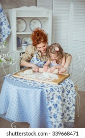 A young mother help to roll a dough to her little daughter  on a kitchen