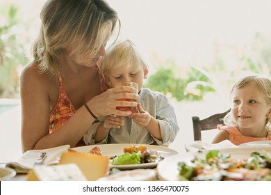 Young mother helping child son to drink from glass, sitting at family table having lunch in holiday villa garden outdoors. Family on sunny summer vacation hotel eating together, leisure lifestyle.