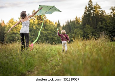 Young mother helping her child to fly a kite as he runs through an autumn grassland.