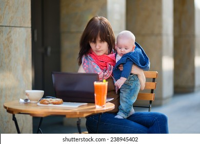 Young mother with her adorable baby boy working or studying on her laptop in cafe