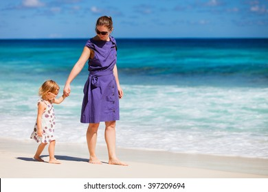 Young mother and her adorable daughter enjoying day at tropical beach on exotic island