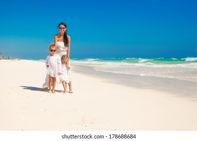 Young mother and her adorable daughters at exotic beach on sunny day