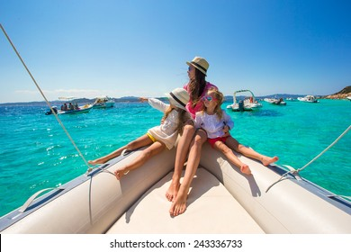 Young mother with her adorable little girls resting on a big boat